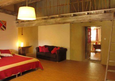 Un lit deux places avec une couverture rouge, un canapé marron, une échelle