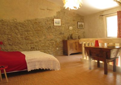 un lit, des meubles anciens baignés de lumière naturel