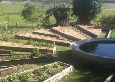 Un potager en arc de cercle autour d'un bassin.